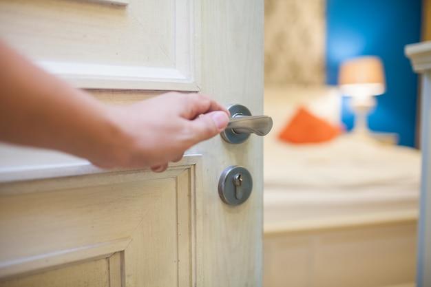 ホテルおよび家の概念のための寝室のドアを開く手 Premium写真