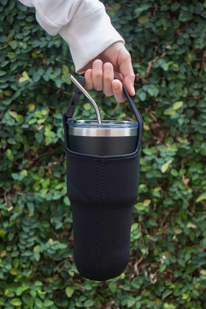 温度を保つために大きな水のボトルを手に Premium写真