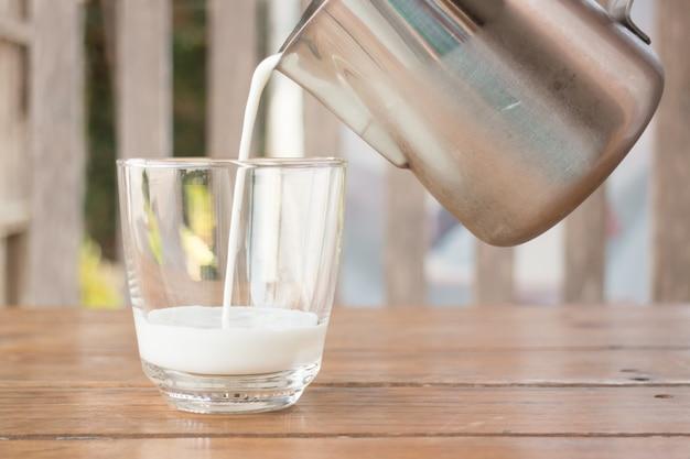 投手のミルクをガラスに注ぐ Premium写真
