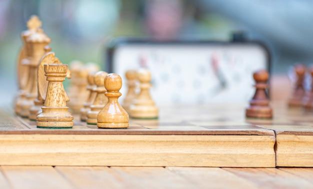 Крупный план шахматной доски с шахмат, старинные, старые, деревянные доски. люди играют в шахматы в городском парке Premium Фотографии