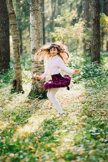 幸せな美しいブルネットの少女は回転し、公園で楽しんでいます Premium写真