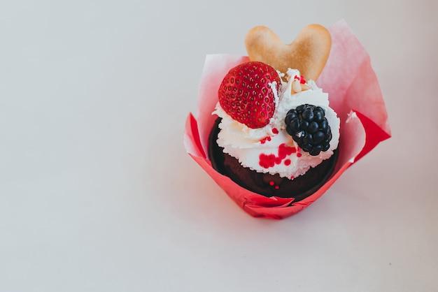 クリームと新鮮な甘いイチゴの果実とブラックベリーのカップケーキ Premium写真