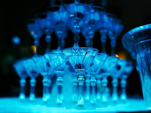 バーテンダーのカクテルグラスの塔ショーのクローズアップ Premium写真
