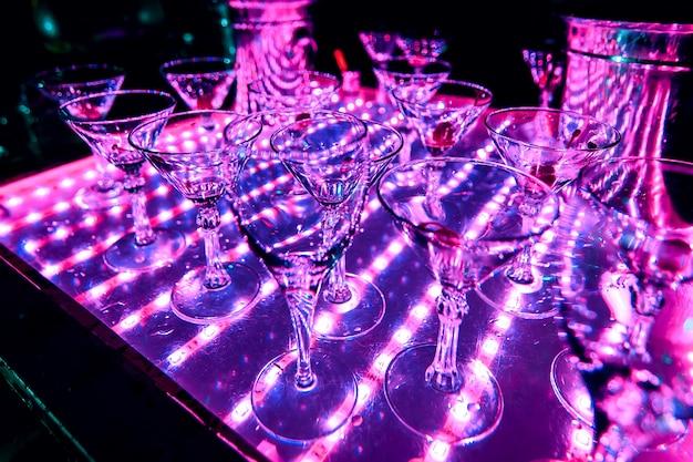 カクテルドリンクから空のグラスの紫外線照明 Premium写真