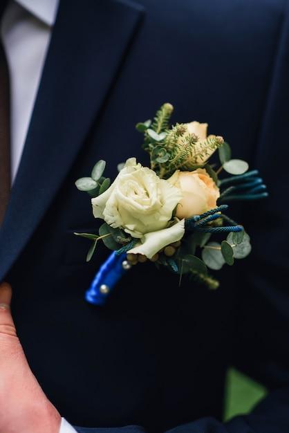 新郎の青いジャケットの襟に白いバラのブートニア Premium写真