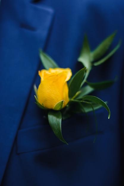 新郎のスーツに新鮮なバラの花のブートニア Premium写真