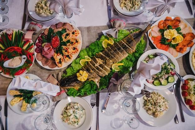 レストランのお祝いテーブルに焼きパイクとその他のスナックを添えた伝統的なロシア料理 Premium写真