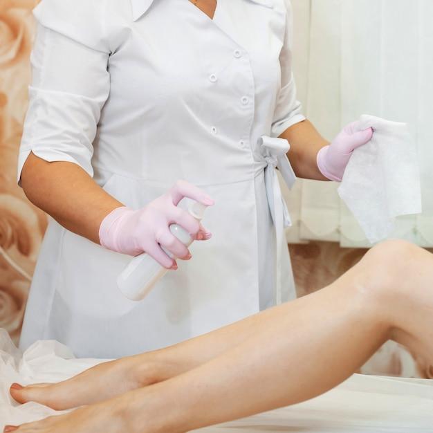シュガー脱毛の手順に細い女性の足を準備する美容師の女性の手 Premium写真
