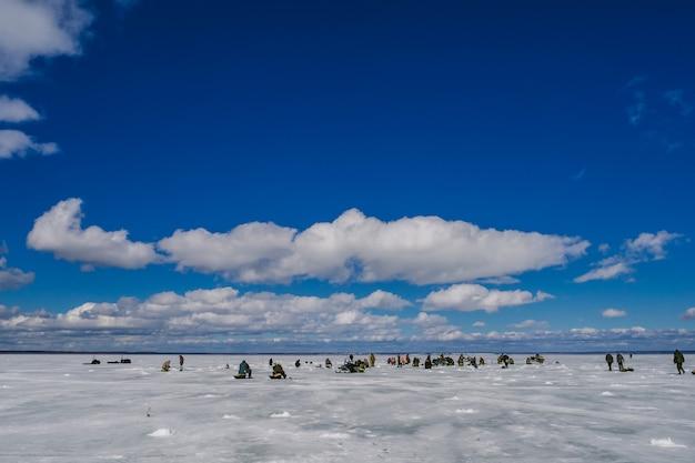 氷の池で釣りをする漁師のグループ Premium写真
