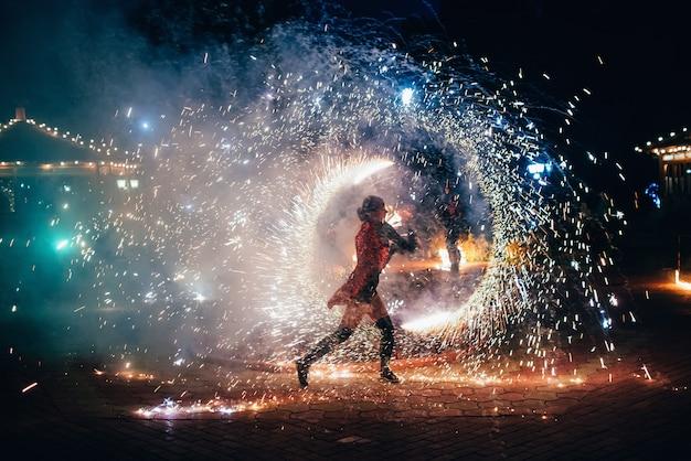 Огненное шоу. девушка крутит огненные сверкающие факелы Premium Фотографии