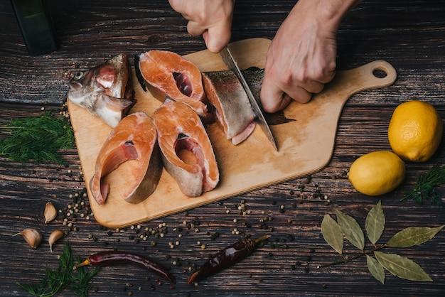 Повар человека режет нож в руках форели. свежая сырая нарезанная красная рыба Premium Фотографии