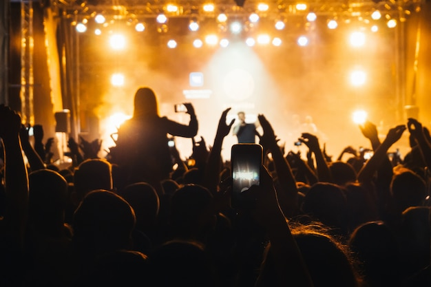 バスタのコンサートで観客の群衆のシルエットと携帯電話を持つ手 Premium写真