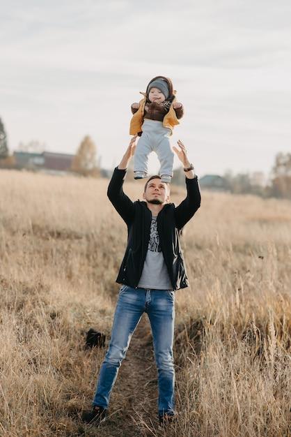 お父さんは自然の中で小さな男の子の息子を投げます Premium写真