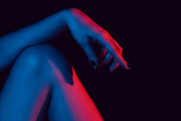 膝の上の女性の手はネオンの光でクローズアップ Premium写真