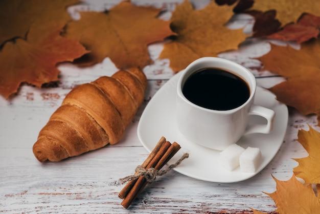 木製のテーブルにクロワッサンとシナモンのスティックとコーヒーのカップ Premium写真