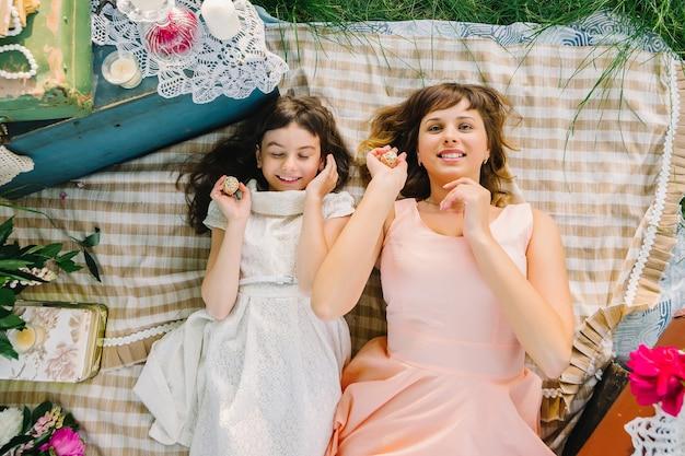 母と娘はピクニックに自然の中でリラックスします。 Premium写真