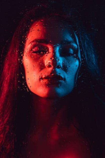 雨滴とガラスの後ろに赤青照明で悲しい少女の肖像画 Premium写真