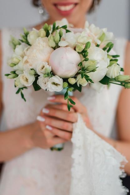 花嫁の手の中に牡丹とウェディングブーケ Premium写真