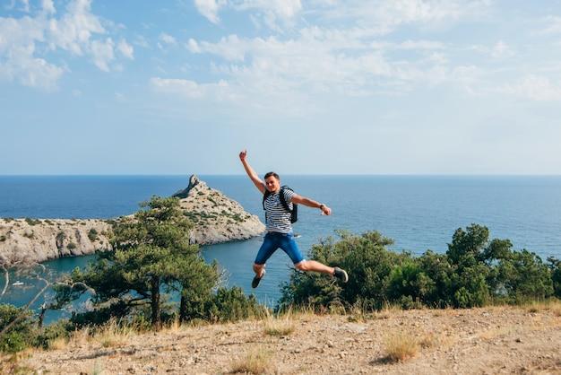 Мужской путешественник радостно и радостно прыгает на природе Premium Фотографии