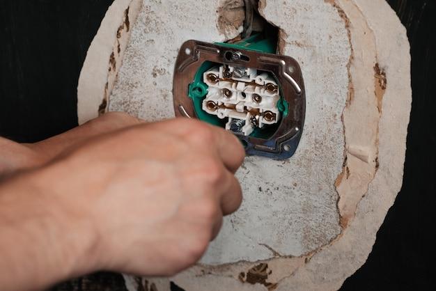 新しいコンセントの交換と取り付け。ドライバー男電気技師の手 Premium写真