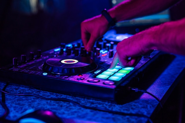 Руки диджея, играющего музыку на микшере на концерте Premium Фотографии
