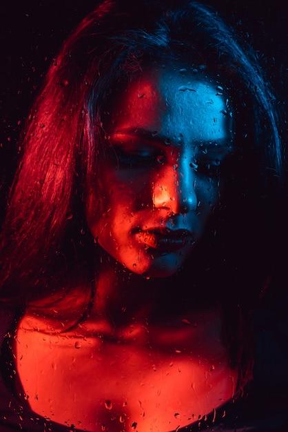 赤青照明と雨滴とガラスを通して悲しい少女の官能的な肖像画 Premium写真