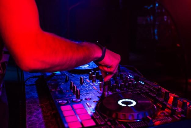 Руки диджея, микширующие музыку на профессиональном контроллере в кабинке Premium Фотографии