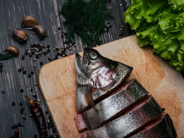 Свежую форель нарезать на кусочки на деревянной доске для приготовления пищи. Premium Фотографии
