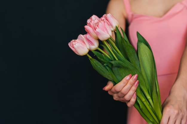 ドレスを着た少女の手にピンクのチューリップの花束 Premium写真