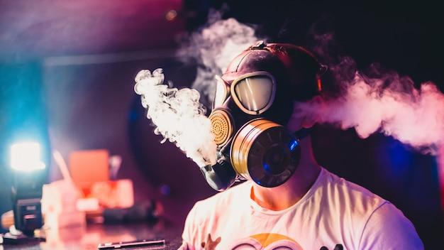 Человек в противогазе курит кальян и вдыхает облако табачного дыма Premium Фотографии