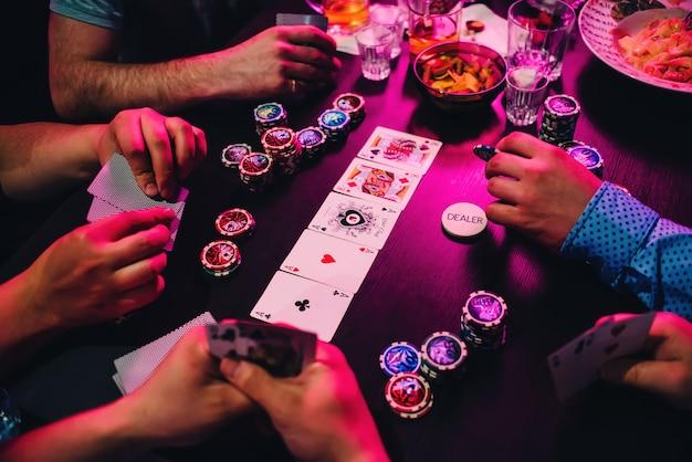 プレイヤーの手でテーブルの上のポーカーカードとチップのゲーム Premium写真