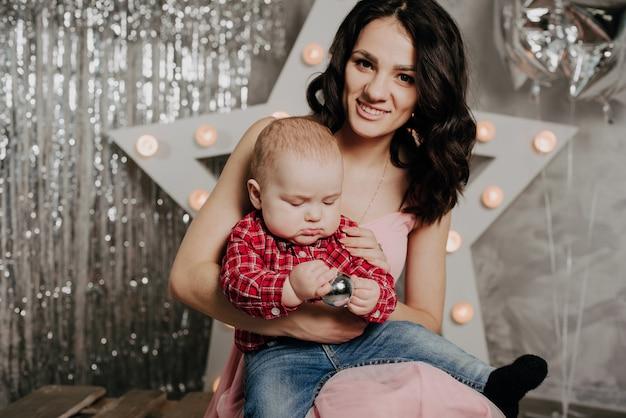 Мама с новорожденным мальчиком сыном на руках рождественские декорации Premium Фотографии