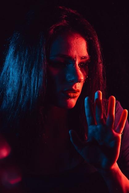 赤と青の照明と雨滴とガラスを通して悲しい少女の官能的な肖像画 Premium写真