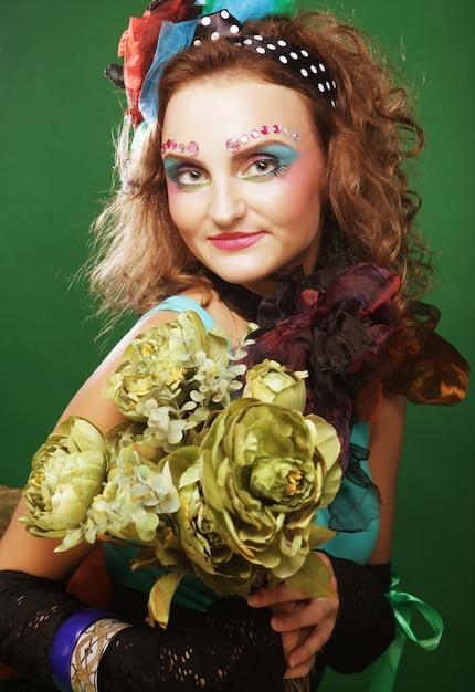 大きな緑の花を保持しているブリクト顔を持つ女性 Premium写真
