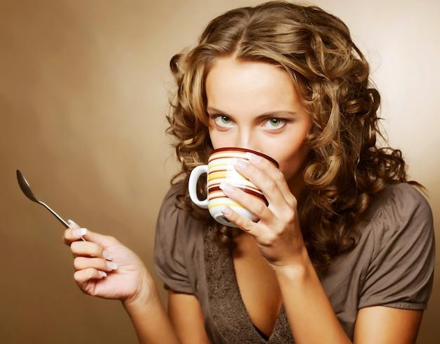 Красивая женщина пьет кофе Premium Фотографии