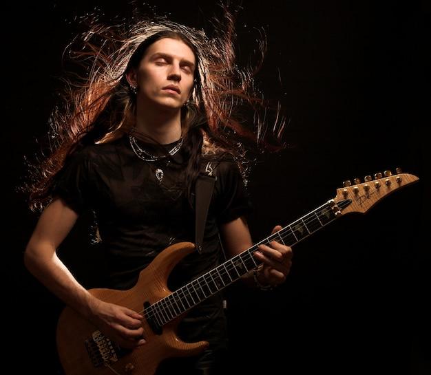 電気ギターを弾く男。髪を巻きます。 Premium写真