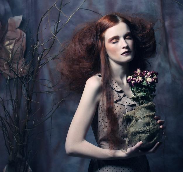 Красивая девушка с сухими розами Premium Фотографии