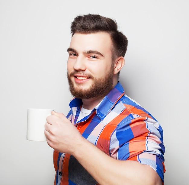 一杯のコーヒーと若いのひげを生やした男 Premium写真