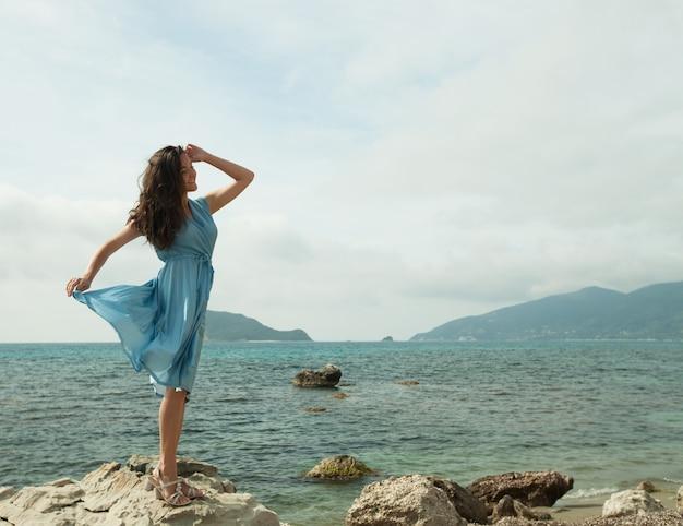 Молодая счастливая женщина позирует возле моря Premium Фотографии