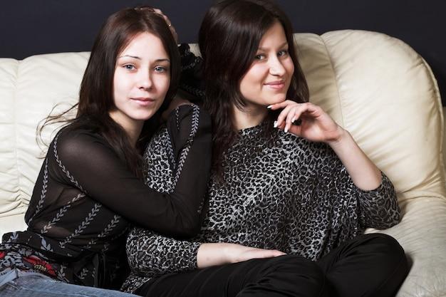 Две красивые модели, одетые в повседневную одежду, сидят на диване Premium Фотографии