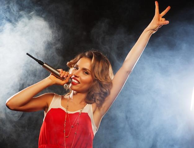 パーティーでマイクに向かって歌っている少女 Premium写真
