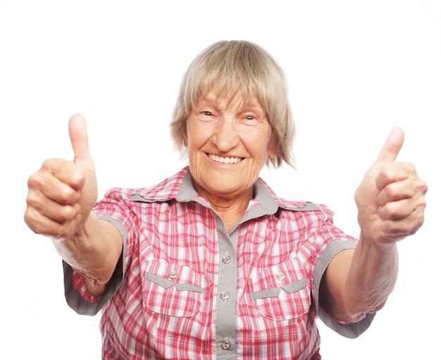 Старая женщина показывает знак ок на белом Premium Фотографии