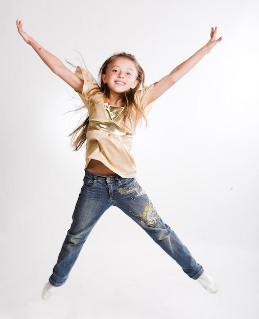 Маленькая девочка прыгает на белом фоне Premium Фотографии