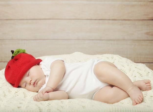 Сладкий сон малыша в красной шапочке Premium Фотографии