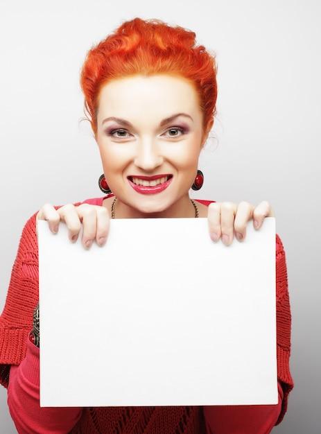 Молодая вскользь женщина счастливая держа пустой знак Premium Фотографии