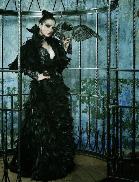 スチールケージでポーズをとってファンタジードレスのファッションモデル。 Premium写真