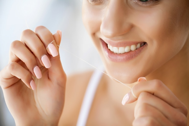 完璧な笑顔で女性の顔のクローズアップ。女の子は特別な糸で歯を掃除しています Premium写真