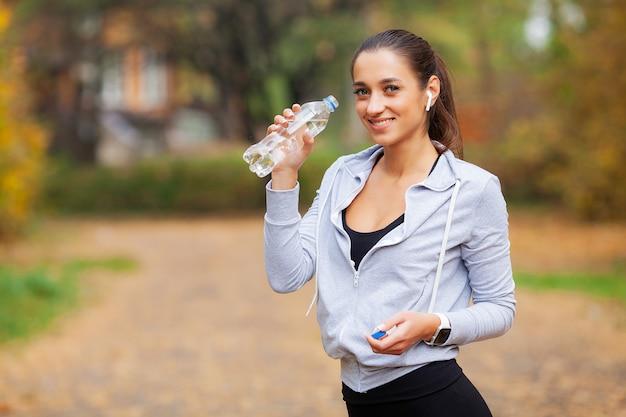 屋外スポーツ実行後の女性飲料水 Premium写真