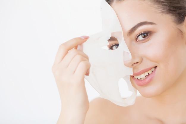 Забота о коже. красивая девушка с маской на лице Premium Фотографии