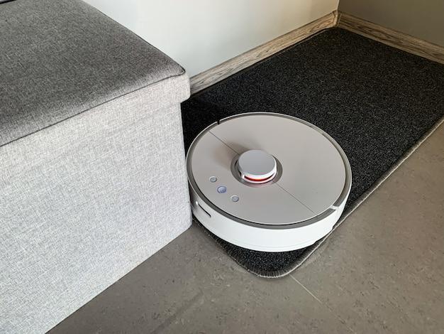 掃除機ロボットは居間の床の上を走ります。 Premium写真